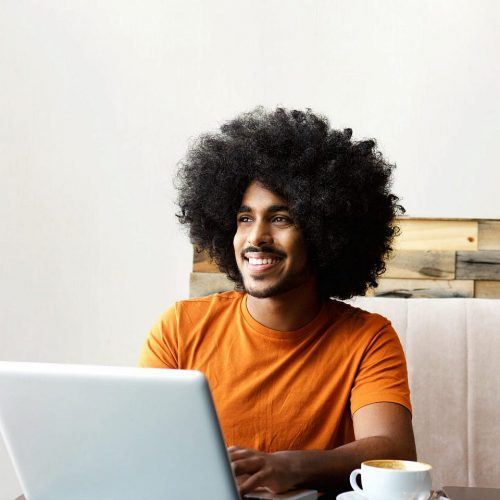 smiling-man-sitting-at-table-with-laptop-P73YT45